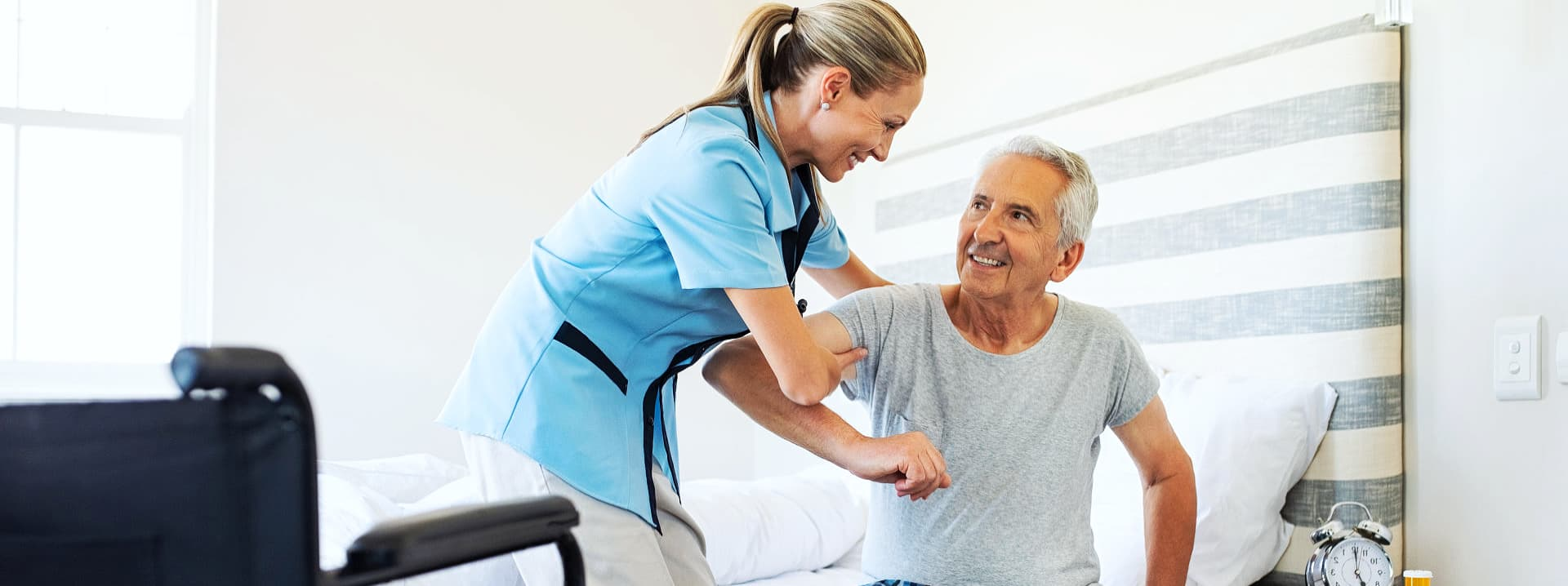 senior man assisted by caregiver to stand