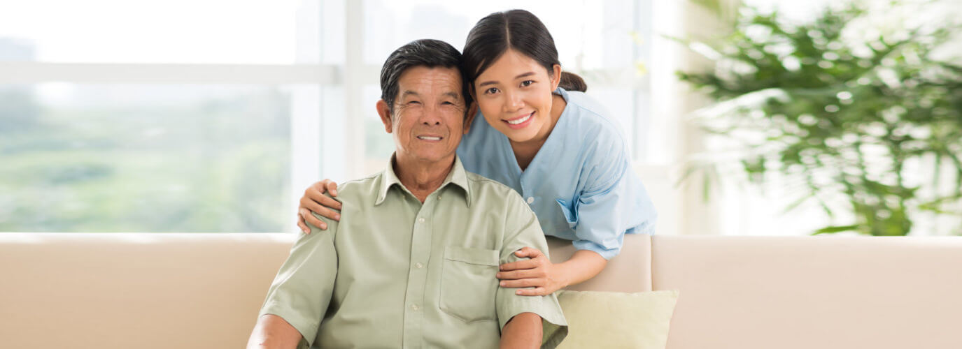 senior man and caregiver smiling