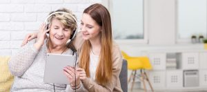 caregiver and senior woman listening to music