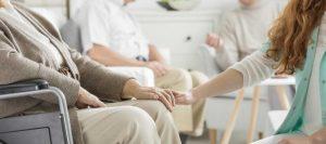caregiver holding senior woman hand