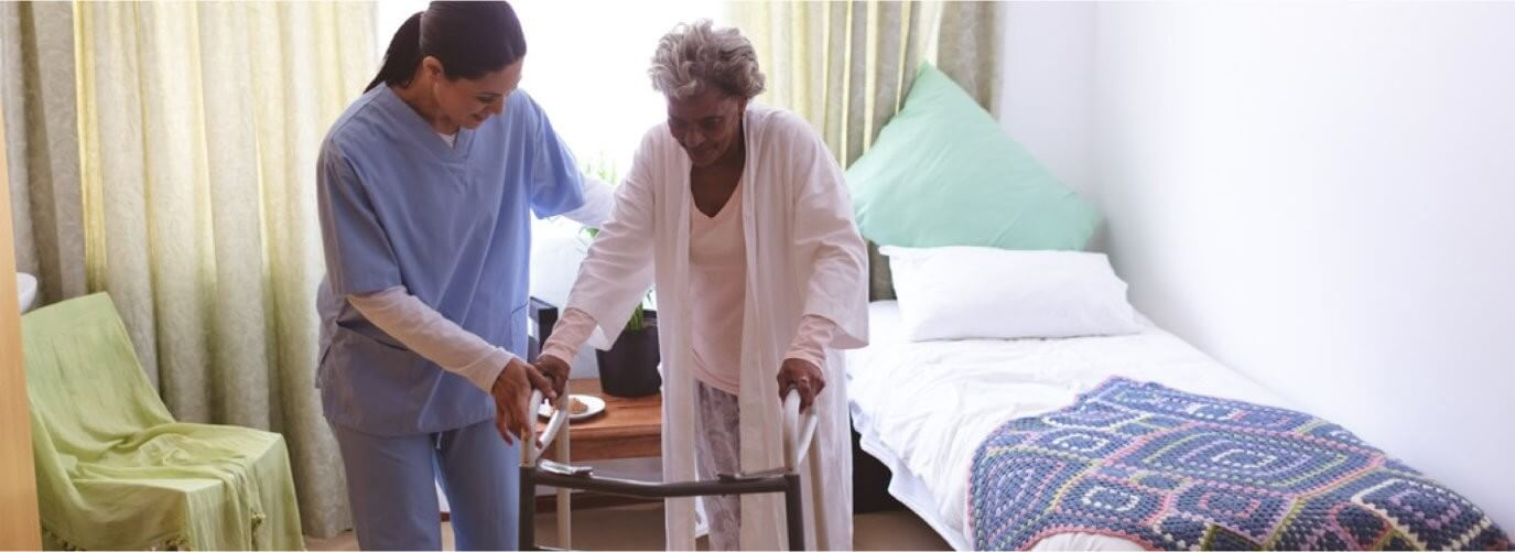 female nurse helping senior mixed race female patient to stand with walker at nursing home