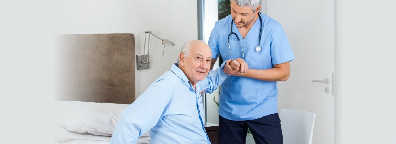 Portrait of senior men being assisted by male caretaker in bedroom at nursing home
