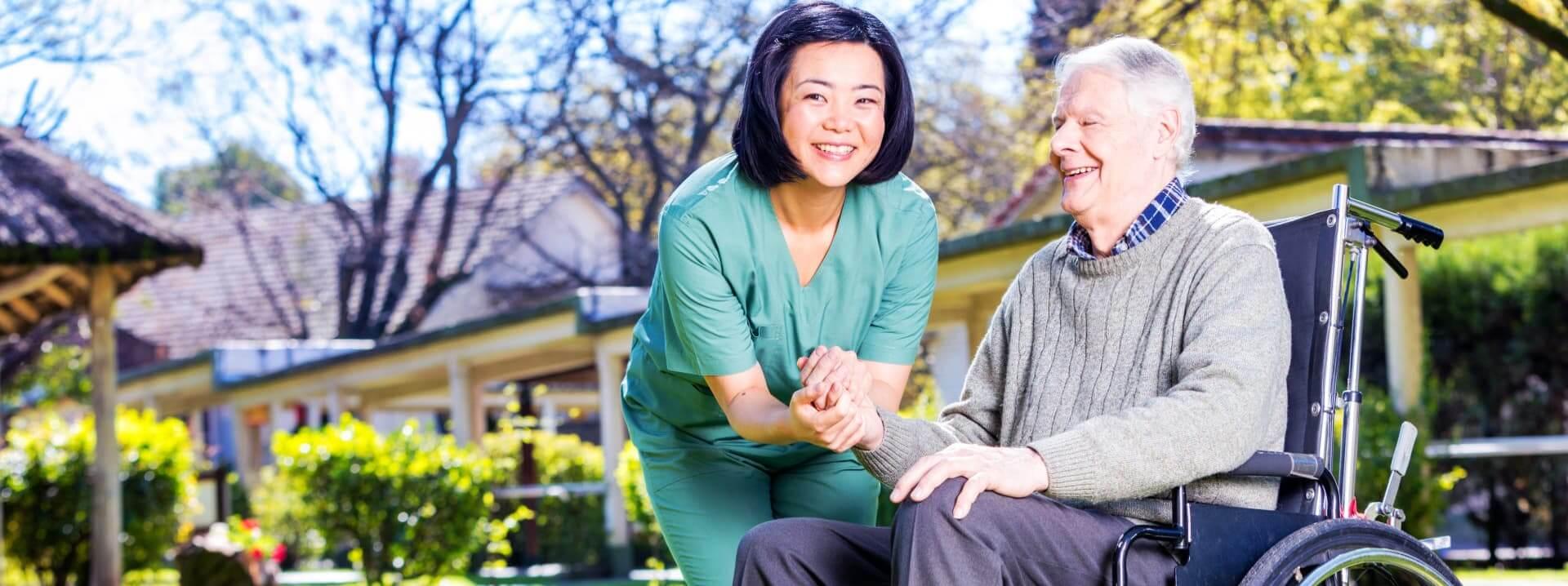 senior man and caregiver outside senior home